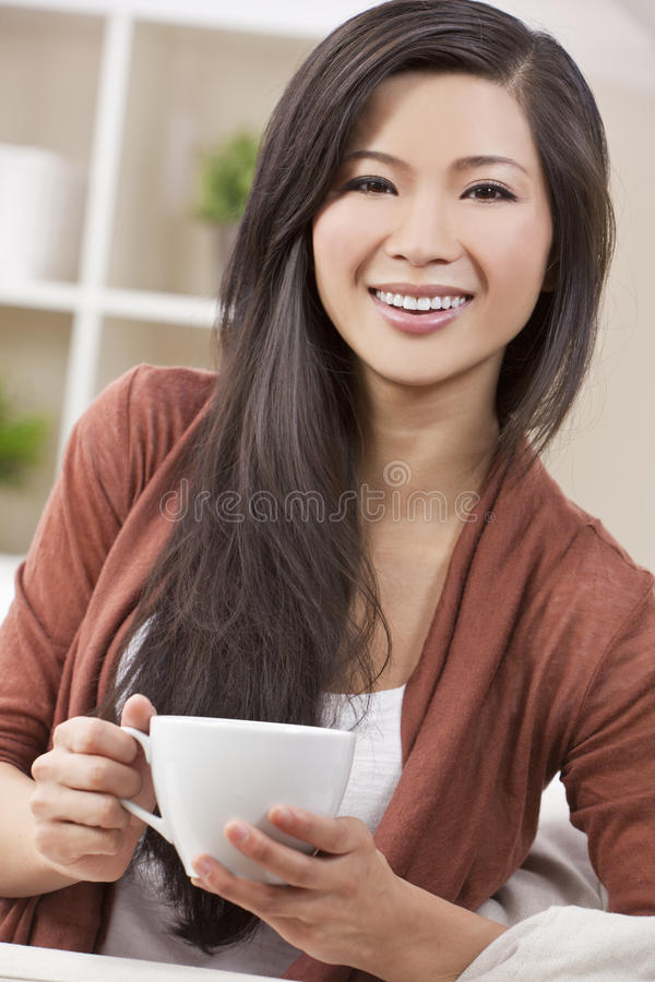 Beautiful Oriental Woman Drinking Tea or Coffee royalty free stock images