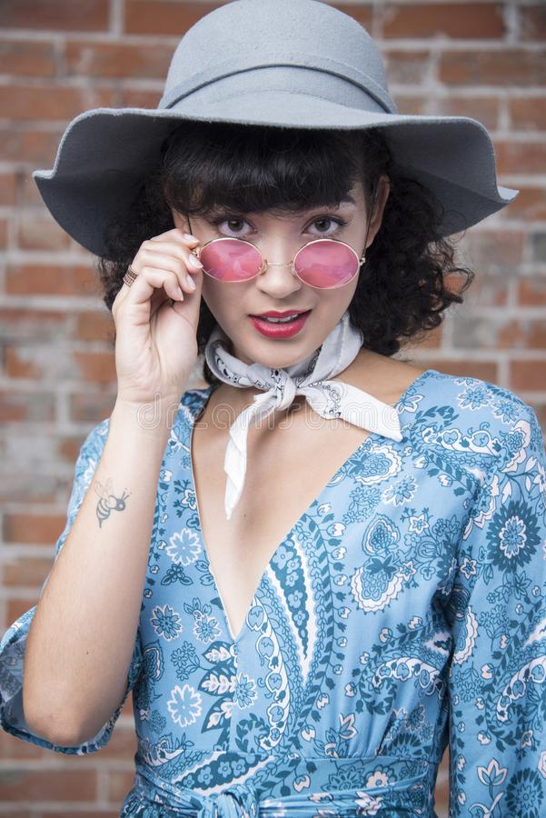 Beautiful oriental woman portrait with rose colored glasses and fashionable sun hat with small tattoo, pretty dress, bandan stock photo