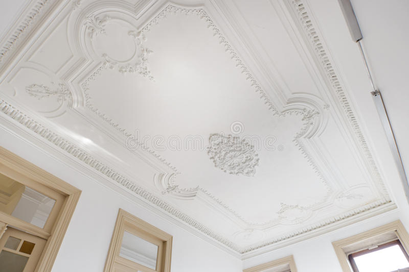 Beautiful Ornamented Ceiling. A beautiful ornamented ceiling in a bright living room stock photos