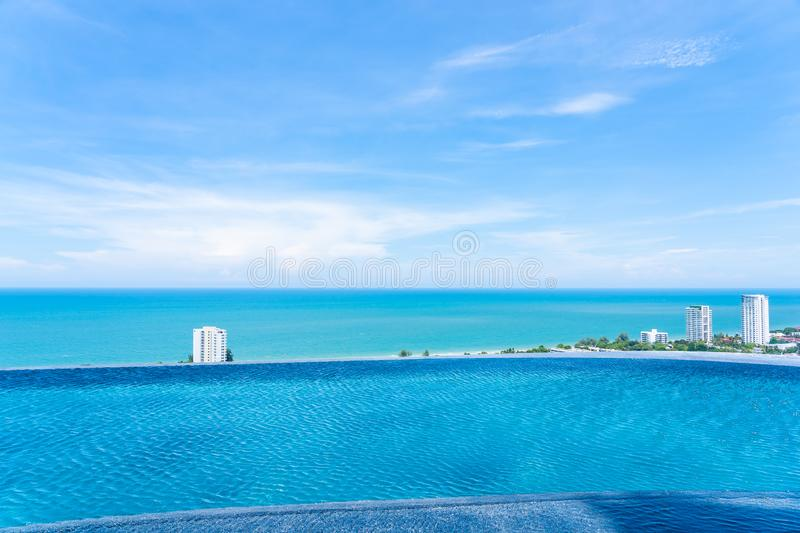 Beautiful outdoor landscape of infinity swimming pool in hotel resort. With sea ocean on white cloud blue sky view for leisure travel in holiday vacation royalty free stock photography