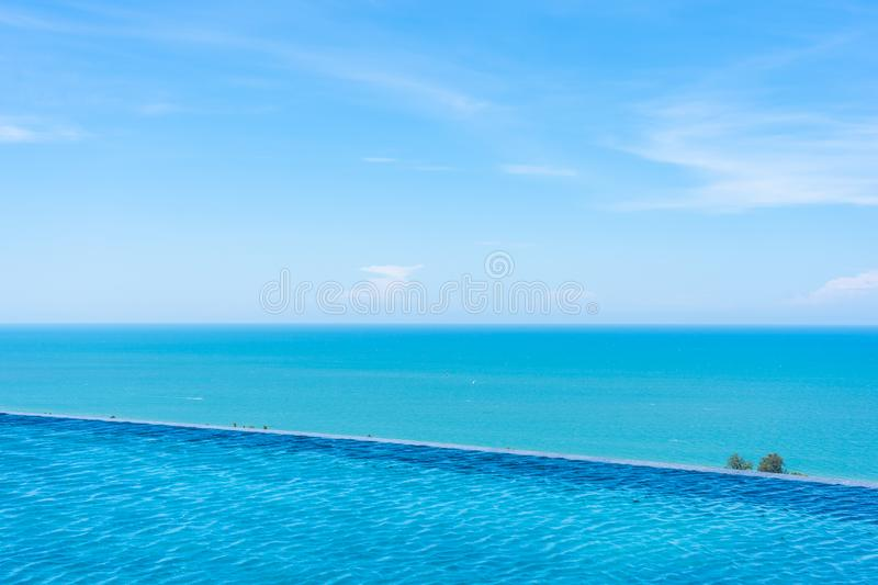 Beautiful outdoor landscape of infinity swimming pool in hotel resort. With sea ocean on white cloud blue sky view for leisure travel in holiday vacation royalty free stock image