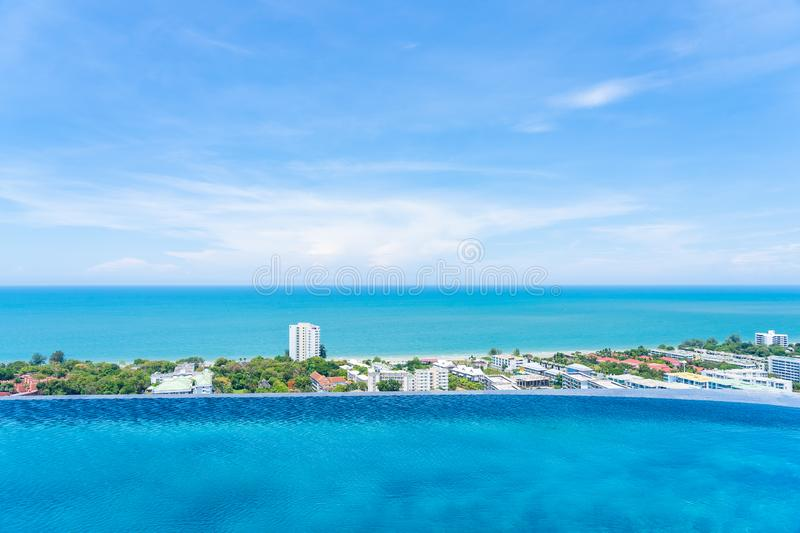 Beautiful outdoor landscape of infinity swimming pool in hotel resort. With sea ocean on white cloud blue sky view for leisure travel in holiday vacation stock photo