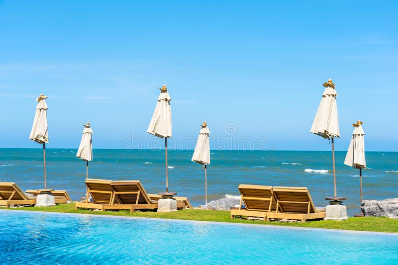 Beautiful outdoor nature landscape with bed deck chair around swimming pool in hotel resort. On blue sky background for travel and vacation concept royalty free stock images