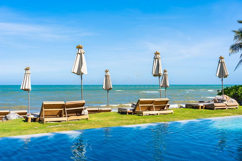 Beautiful outdoor nature landscape with bed deck chair around swimming pool in hotel resort. On blue sky background for travel and vacation concept stock images