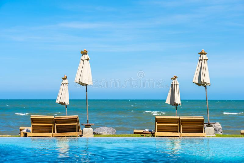 Beautiful outdoor nature landscape with bed deck chair around swimming pool in hotel resort. On blue sky background for travel and vacation concept royalty free stock photos