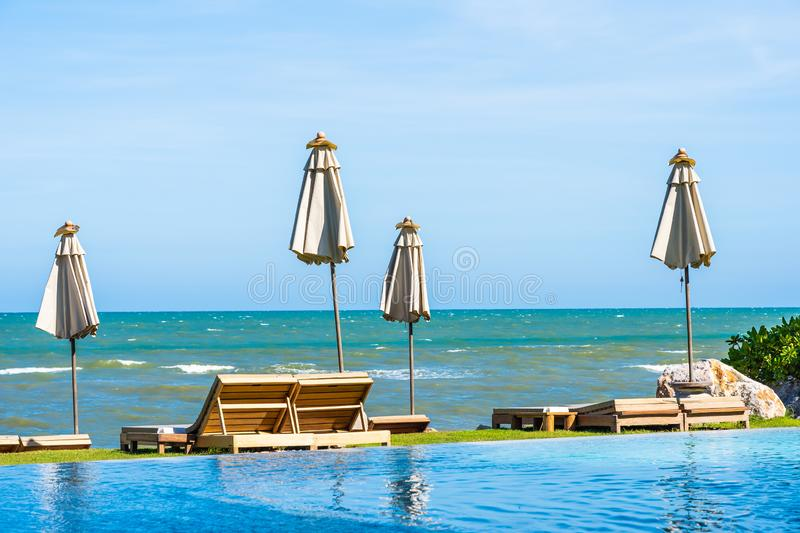Beautiful outdoor nature landscape with bed deck chair around swimming pool in hotel resort. On blue sky background for travel and vacation concept stock photo