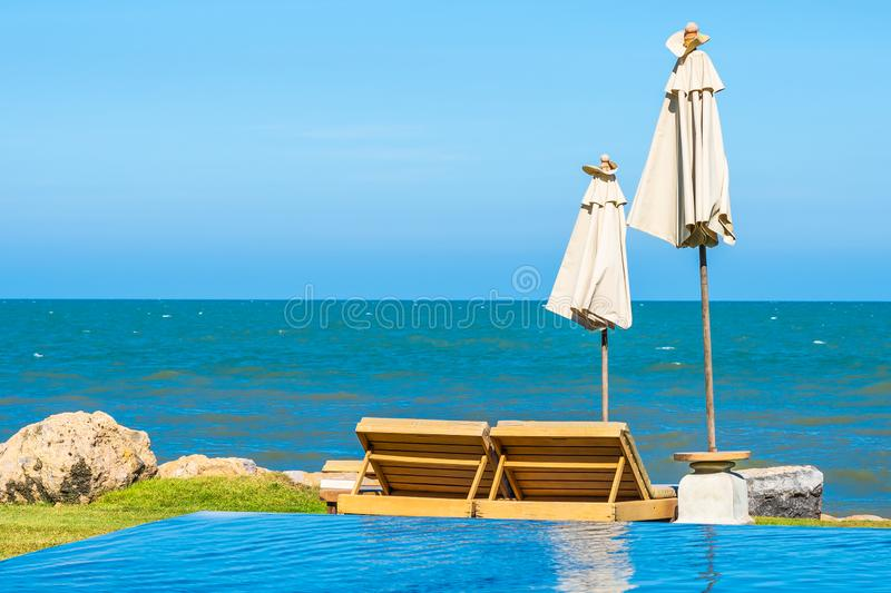 Beautiful outdoor nature landscape with bed deck chair around swimming pool in hotel resort. On blue sky background for travel and vacation concept royalty free stock image