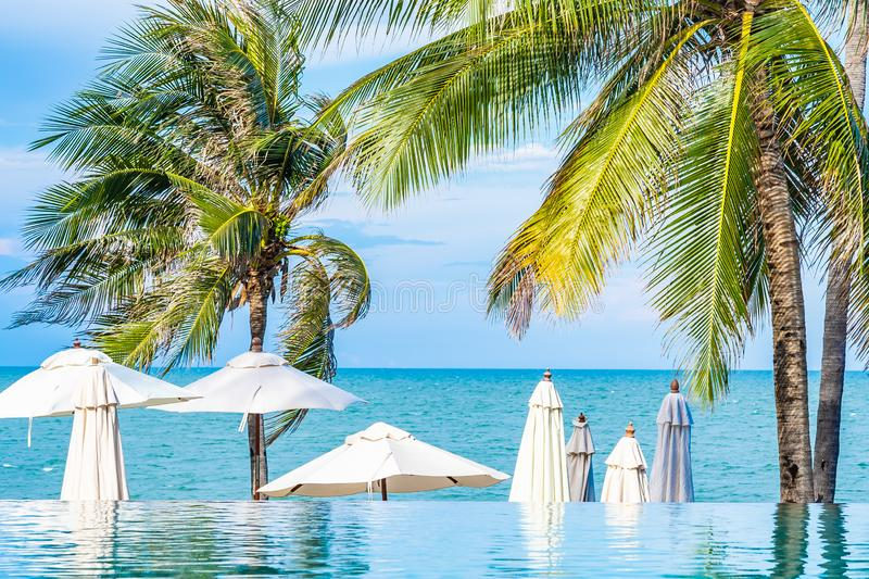 Beautiful outdoor nature with umbrella chair and coconut palm tree around swimming pool in hotel and resort. For holiday vacation concept stock images