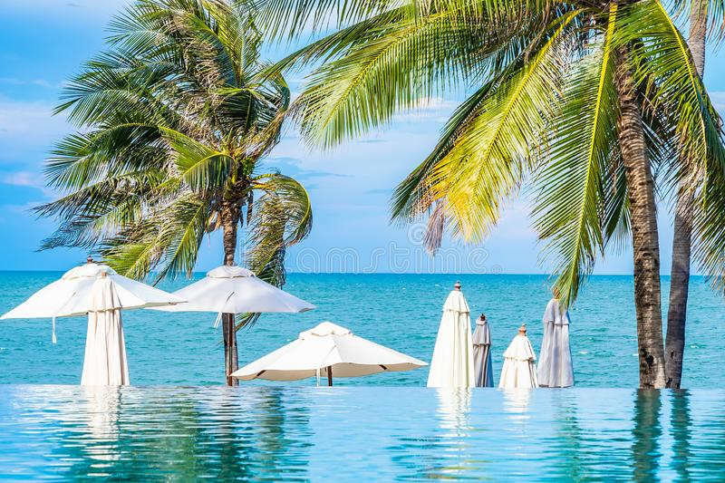 Beautiful outdoor nature with umbrella chair and coconut palm tree around swimming pool in hotel and resort. For holiday vacation concept stock photography