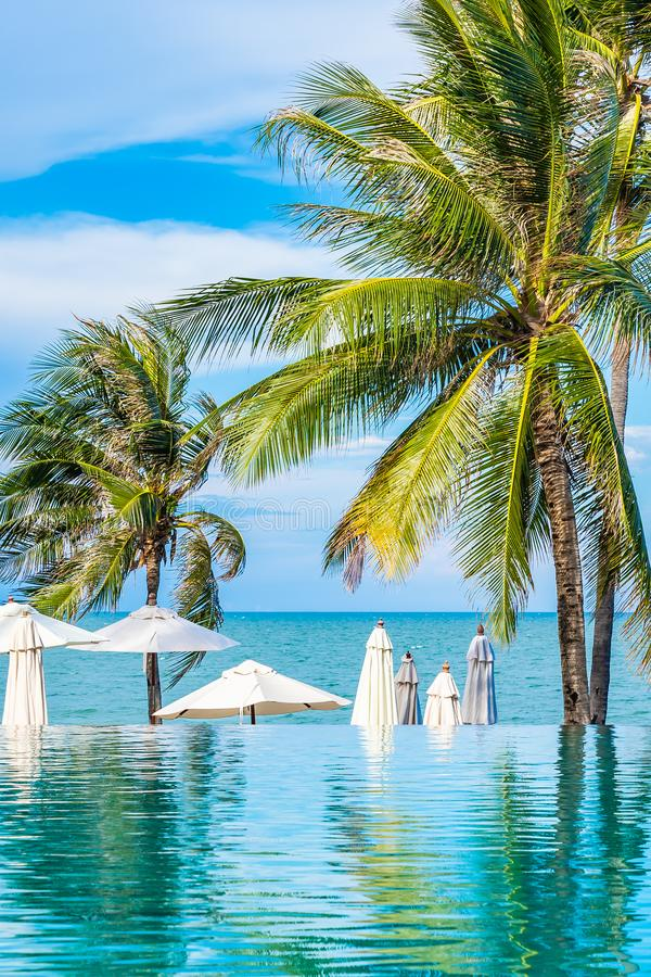 Beautiful outdoor nature with umbrella chair and coconut palm tree around swimming pool in hotel and resort. For holiday vacation concept stock photos