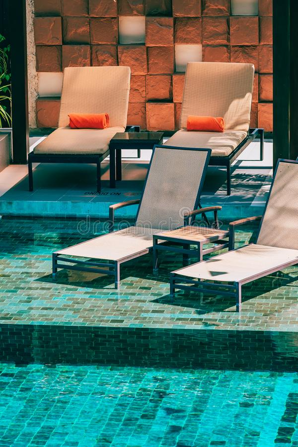 Beautiful outdoor swimming pool in hotel and resort with chair and deck for leisure vacation. And travel royalty free stock photography