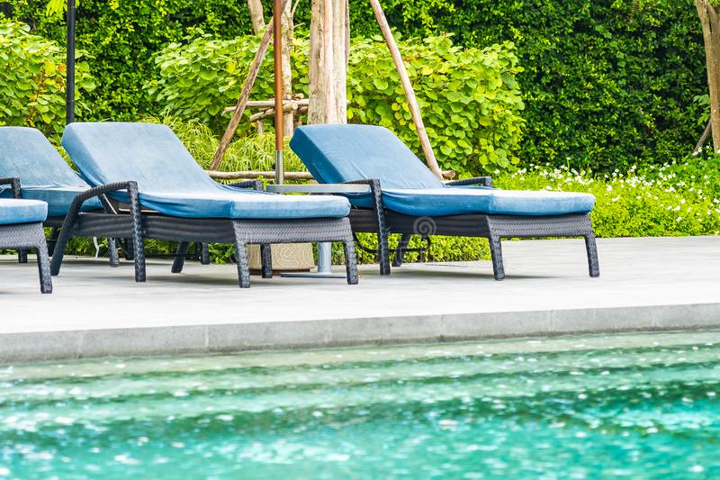 Beautiful outdoor swimming pool in hotel and resort with chair and deck for leisure vacation. And travel stock photo