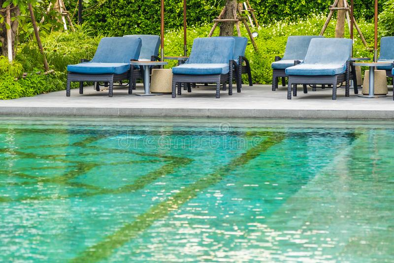 Beautiful outdoor swimming pool in hotel and resort with chair and deck for leisure vacation. And travel royalty free stock photo