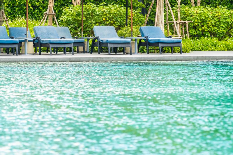Beautiful outdoor swimming pool in hotel and resort with chair and deck for leisure vacation. And travel stock photography