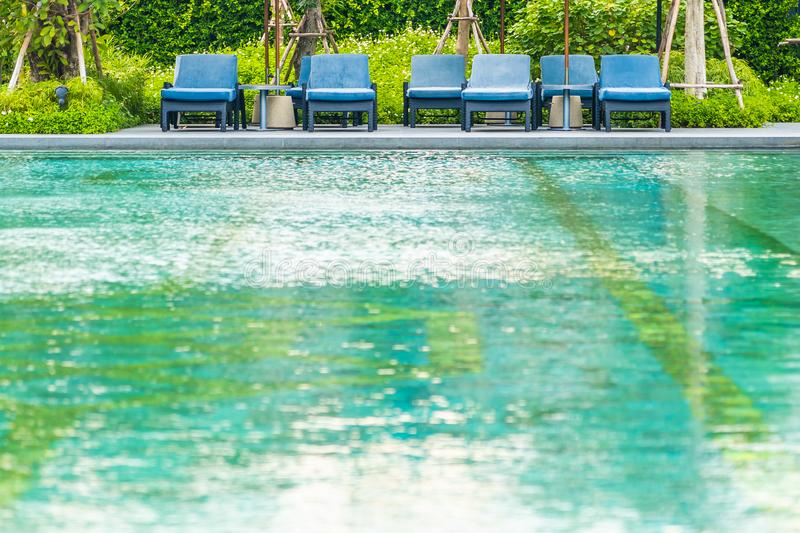 Beautiful outdoor swimming pool in hotel and resort with chair and deck for leisure vacation. And travel stock photos