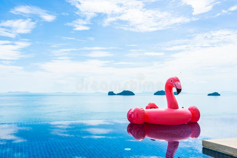 Beautiful outdoor swimming pool in hotel resort with flamingo float around sea ocean white cloud on blue sky. For holiday vacation travel concept royalty free stock photos