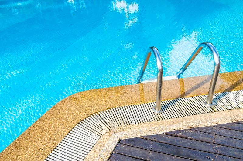 Beautiful outdoor swimming pool in hotel resort with stair. For leisure relax in holiday vacation royalty free stock photography