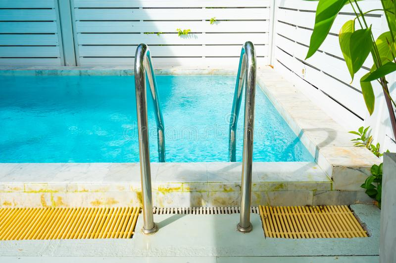Beautiful outdoor swimming pool in hotel resort with stair. For leisure relax in holiday vacation royalty free stock photos