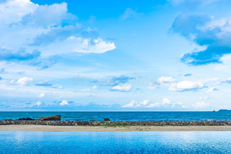 Beautiful outdoor swimming pool in hotel resort with white cloud and blue sky for leisure relax. In holiday vacation royalty free stock photography