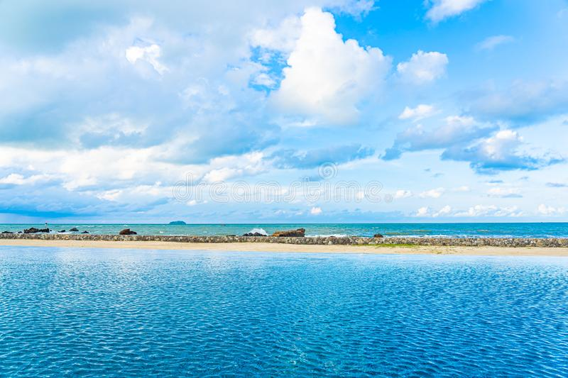 Beautiful outdoor swimming pool in hotel resort with white cloud and blue sky for leisure relax. In holiday vacation stock images