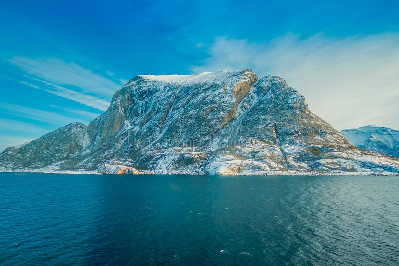 Beautiful outdoor view of coastal scenes of huge mountain covered with snow on Hurtigruten voyage. In Norway stock photo