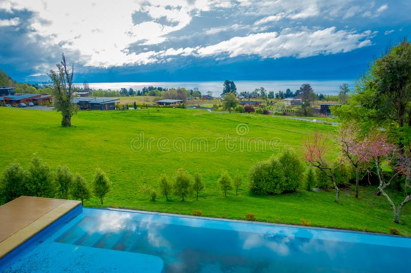 Beautiful outdoor view of infinity swimming pool with a gorgoues green grassland and lake in the horizont located at. Pucon city, Chile stock photos