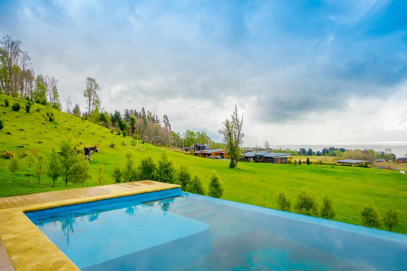 Beautiful outdoor view of infinity swimming pool with a gorgoues green grassland and lake in the horizont located at. Pucon city, Chile stock photo
