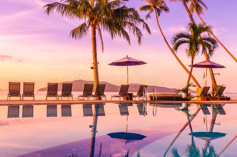 Beautiful outdoor view with umbrella and chair around swimming pool in luxury hotel and resort. At sunrise time for travel and vacation royalty free stock images