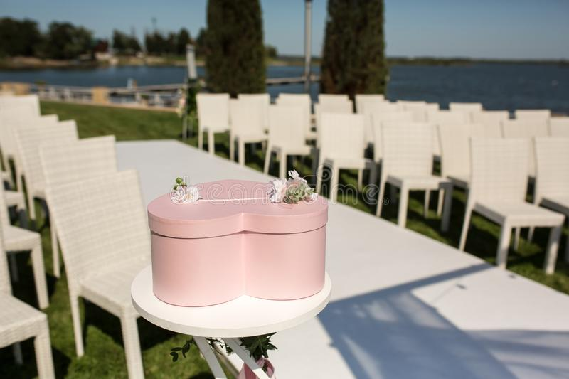 Beautiful outgoing wedding set up. Jewish Hupa  on romantic wedding ceremony , wedding outdoor on the lawn. Wedding decor. A pink. Box for presents in the shape royalty free stock photo