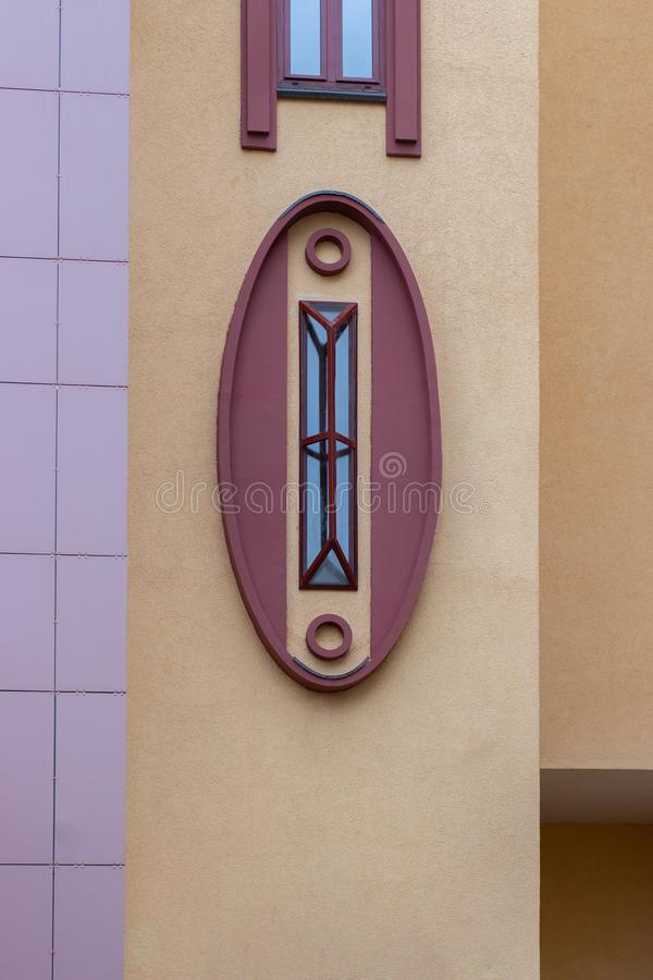 A beautiful oval window with an unusual design, the facade of a modern building. Rectangular metal grill on an oval window stock photography