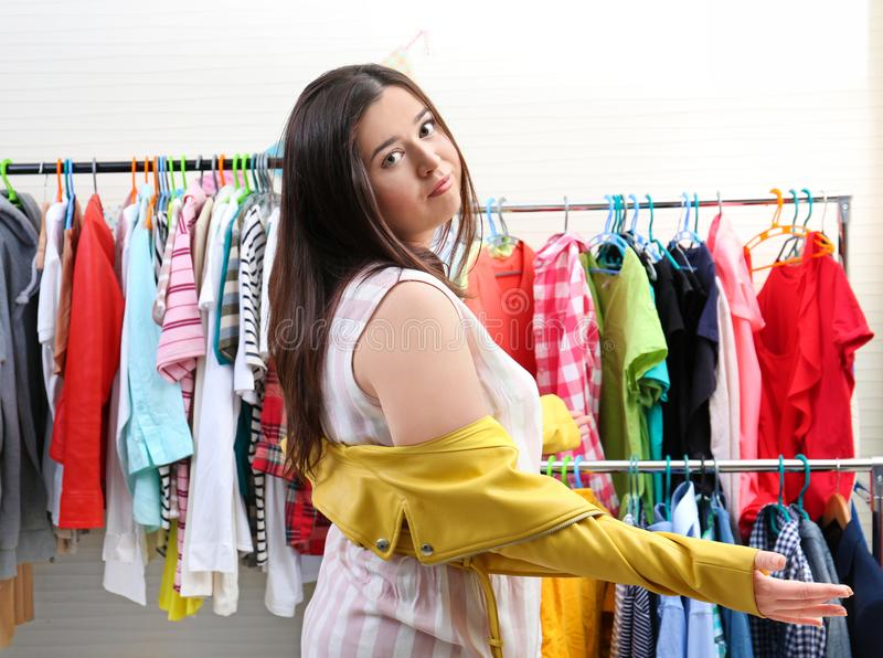 Beautiful overweight woman trying to put on small-sized jacket royalty free stock images
