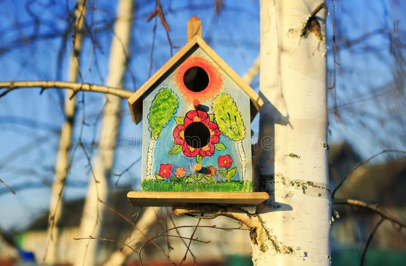 Beautiful painted bird house birdhouse hanging on birch tree in stock photography