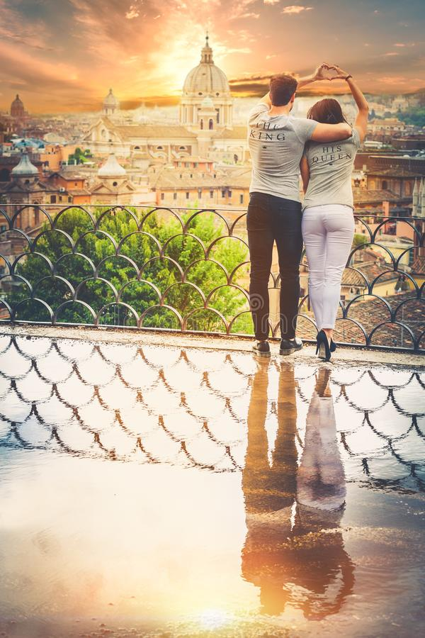 Romantic couple in Rome city, Italy. Loving relationship. Passion and love. A beautiful pair embrace on a terrace with a reflection in a puddle. Behind them the