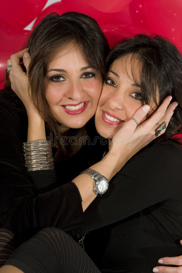Beautiful pair models girls sisters hug closely stock photo
