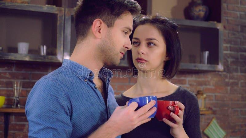 Beautiful pair speaking enjoy tea in flat. stock image