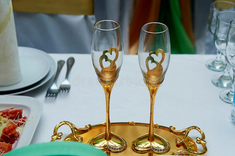 Beautiful pair of wedding goblets with gold . On a tray. royalty free stock photography