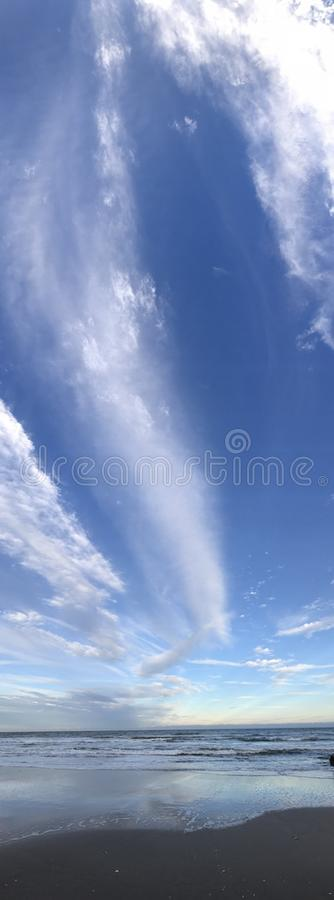 A beautiful panorama of blue skies over the Atlantic Ocean in Florida. The ocean is a striking blue as sunset nears in Central Florida. The clouds are serene and stock photos