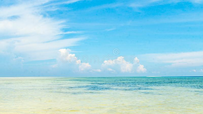 Beautiful panorama of horizon with hazy white tropical clouds above tropical blue empty sea. royalty free stock photo