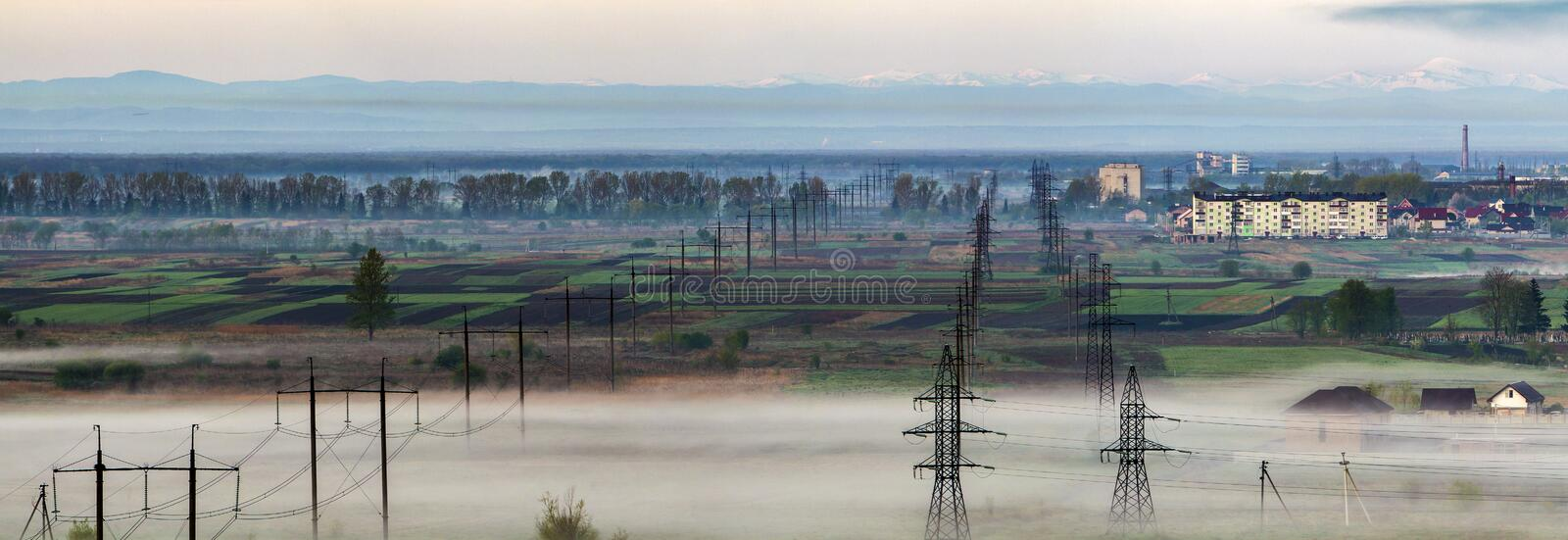 Beautiful panorama of long electric high voltage power line rows. Stretching to horizon through spring fields and trees under dense morning fog on distant stock image