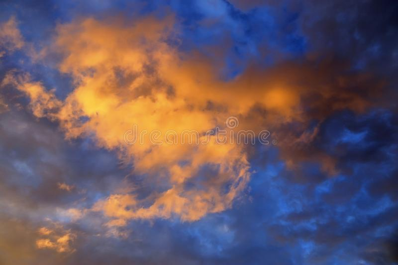 Beautiful panorama of orange and yellow clouds at sunrise/sunset on a blue sky in high resolution royalty free stock photo