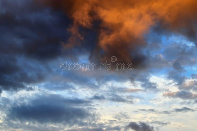 Beautiful panorama of orange and yellow clouds at sunrise/sunset on a blue sky in high resolution royalty free stock image