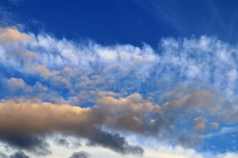 Beautiful panorama of orange and yellow clouds at sunrise/sunset on a blue sky in high resolution royalty free stock images