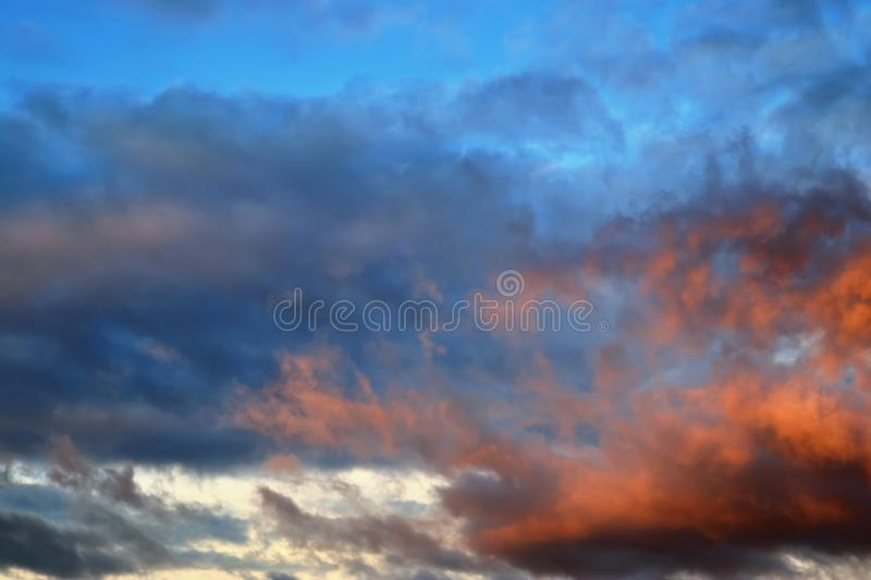 Beautiful panorama of orange and yellow clouds at sunrise/sunset on a blue sky in high resolution stock image