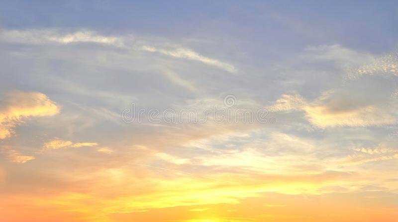 Beautiful panorama of orange and yellow cloudscapes at sunrise/sunset  on a blue sky in high resolution royalty free stock photos