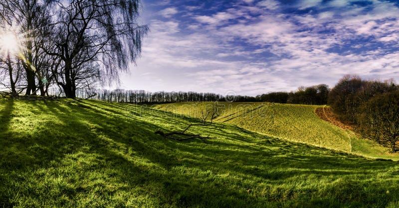 Beautiful panorama of rolling hills, green grass and blue sky stock photos
