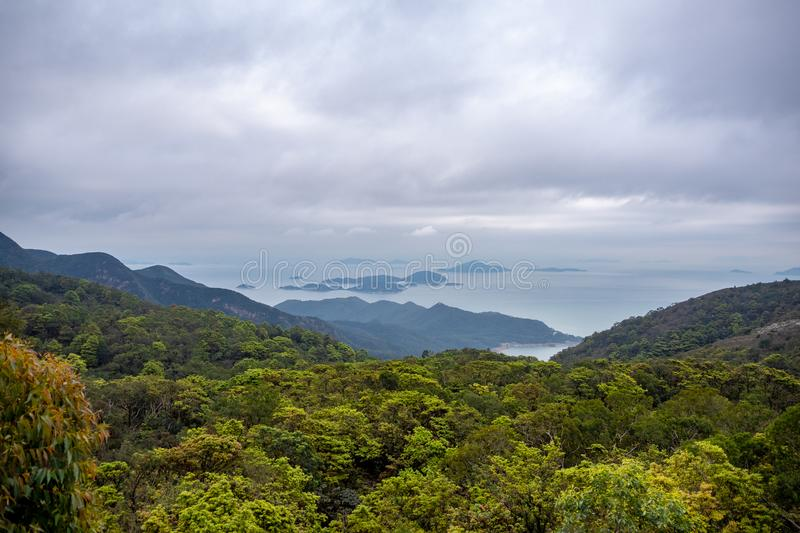Beautiful panorama view of a mountain full of fresh green trees and sea with clouds sky stock photo