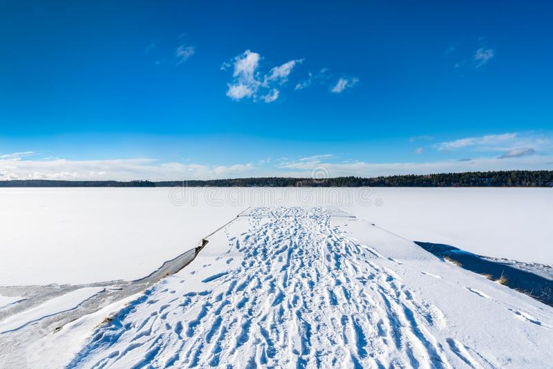 Beautiful panorama winter landscape view of blue sky and frozen snow lake and a jetty with footprints in the snow. stock photos