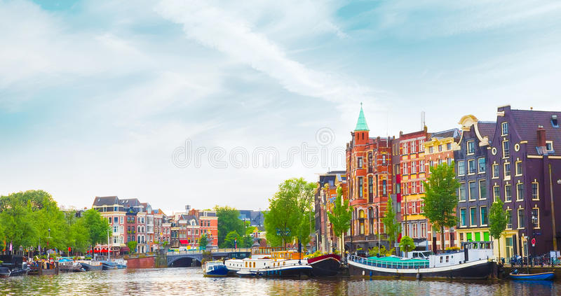Beautiful panoramic cityscape of Amsterdam. Capital of Netherlands. Colorful view of the canal with an amazing building in summer. Horizontal Image royalty free stock images