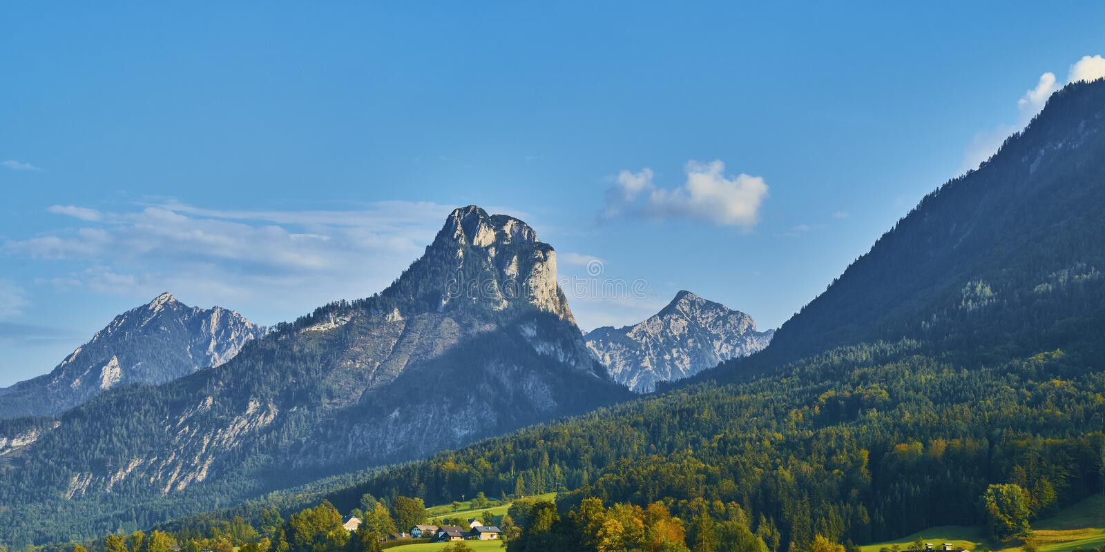 Beautiful panoramic landscape with lush green grass land and Alpine mountains near Wolfgangsee lake in Austria royalty free stock photography