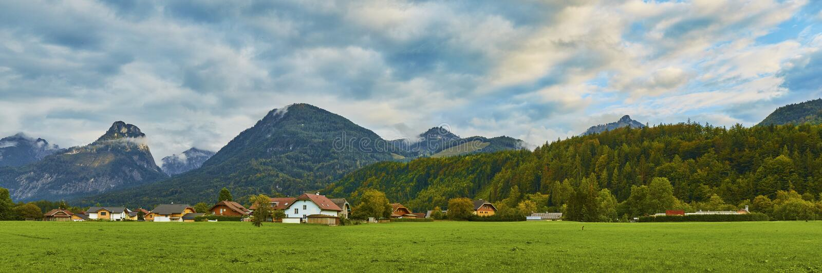 Beautiful panoramic landscape with lush green grass land and Alpine mountains near Wolfgangsee lake in Austria stock photos